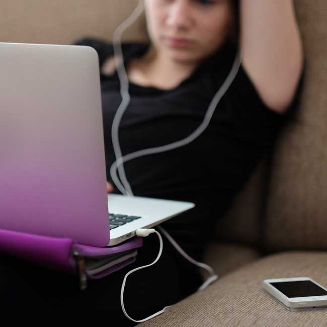 Teen with headphones and laptop